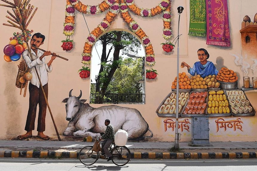 A cyclist riding past colourful murals in New Delhi's Lodhi art district, the first public art district in India. Located in the capital city's Lodhi colony, the art district is home to many murals by some 35 artists from India and around the world.