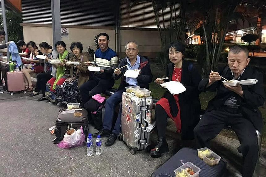 A posting on Facebook showing tourists eating packed food during a long wait to clear Customs at the Sultan Abu Bakar Complex in Johor.