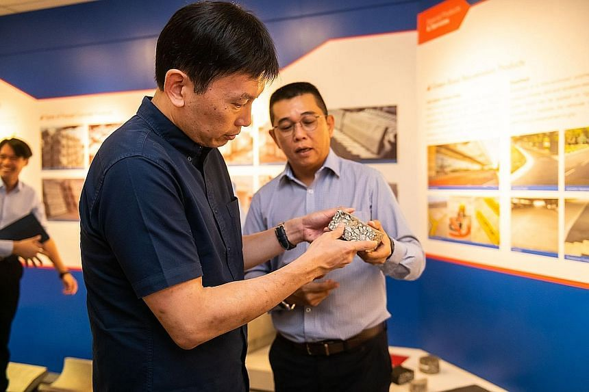 Samwoh chief executive officer Eric Soh (right) handing Senior Minister of State for Trade and Industry and Education Chee Hong Tat a sample of recycled material in the Samwoh Innovation Centre at Samwoh Eco-Green Building.