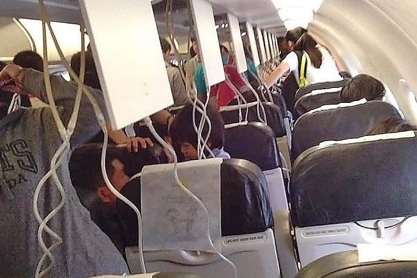 The oxygen masks were activated (above) during the Scoot flight from Singapore to Taipei when it experienced abnormal cabin pressure during the descent and the aircrew told passengers to put them on (below).