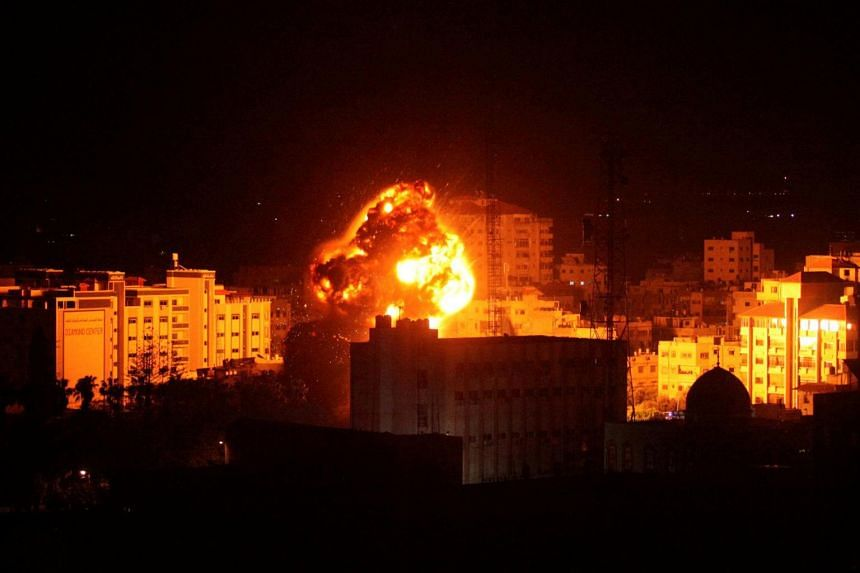 Flame and smoke are seen during an Israeli air strike in Gaza City, on March 25, 2019.