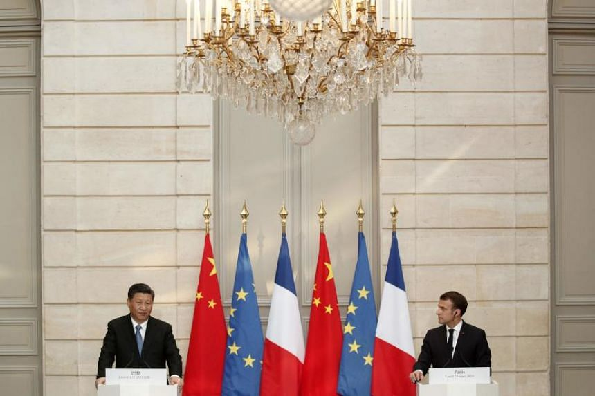 French President Emmanuel Macron (right) and Chinese President Xi Jinping hold a press conference after their meeting at the Elysee Palace in Paris, on March 25, 2019.