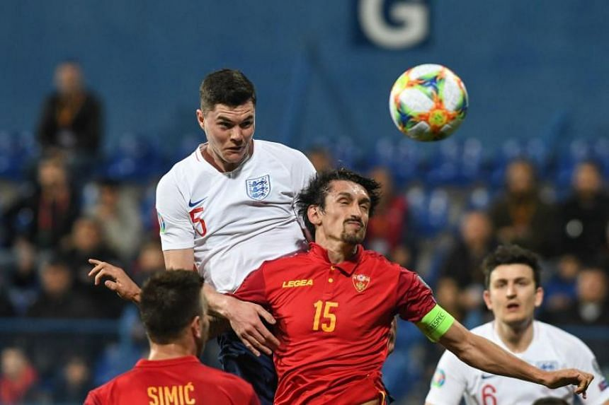 England's defender Michael Keane (left) scores a goal during the Euro 2020 football qualification match between Montenegro and England at Podgorica City Stadium on March 25, 2019 in Podgorica, Montenegro.