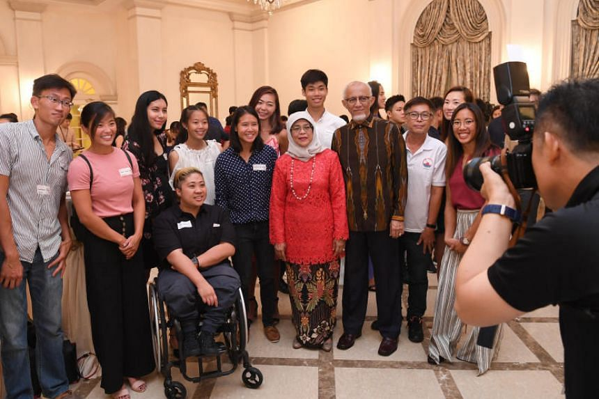 President Halimah Yacob and her husband Mohamed Abdullah Alhabshee with athletes and officials who participated in five major overseas games in 2018 at a dinner reception at the Istana on March 26, 2019.