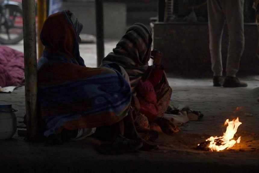 Homeless people sit next to a small fire on a cold foggy morning in New Delhi, India on Feb 4, 2019.