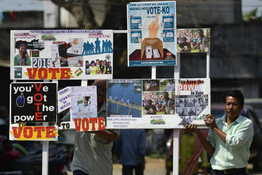 Indian election officials carry election information material during a voters' awareness campaign in Tura, India. Authorities have confiscated 4.4 million litres of liquor and 1.5 billion rupees in cash considered suspicious so far, the election c