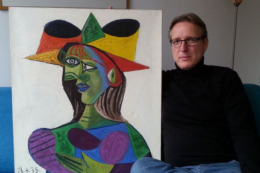 """Art detective Arthur Brand posing with the Picasso painting """"Buste de Femme (Dora Maar), after he managed to acquire it years after it was stolen in 1999."""