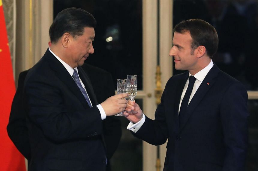 Chinese President Xi Jinping (left) and French President Emmanuel Macron toast during a state dinner at the Elysee Palace in Paris, France, on March 25, 2019.