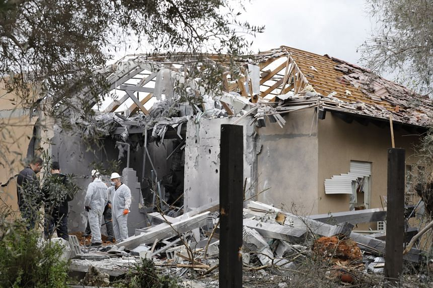 Israeli police examining a house in Moshav Mishmeret, north of Tel Aviv, yesterday that was hit by a rocket that the military said was launched by Hamas from about 120km away. There has been no claim of responsibility for the early morning strike.