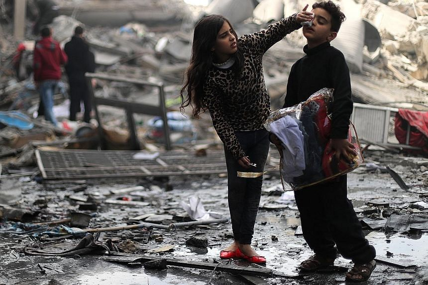 A Palestinian girl cleaning her brother's face outside their destroyed house after an Israeli missile targeted a nearby Hamas site in Gaza yesterday.