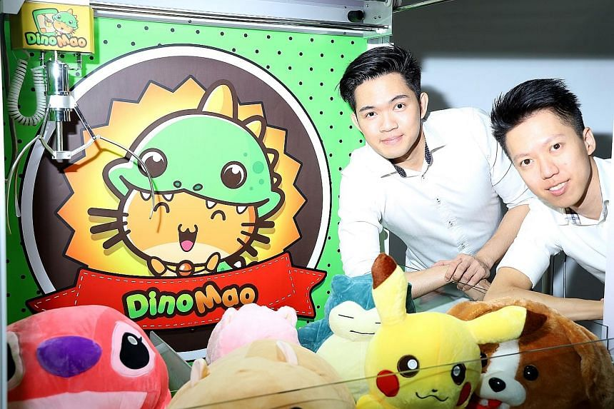 DinoMao founders Jeremy Foo (left) and Jacky Goh with one of their claw machines.