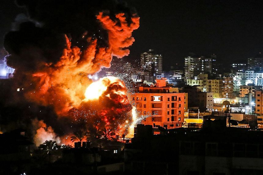 Fire and smoke billowing from buildings in Gaza City after Israeli airstrikes on Monday. One of the targets of the airstrikes was the office of Hamas chief Ismail Haniyeh (below), although he was likely to have been evacuated before the building was