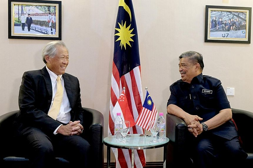 Singapore's Defence Minister Ng Eng Hen exchanging views with Malaysia's Minister of Defence Mohamad Sabu on the sidelines of the Langkawi International Maritime and Aerospace Exhibition yesterday.
