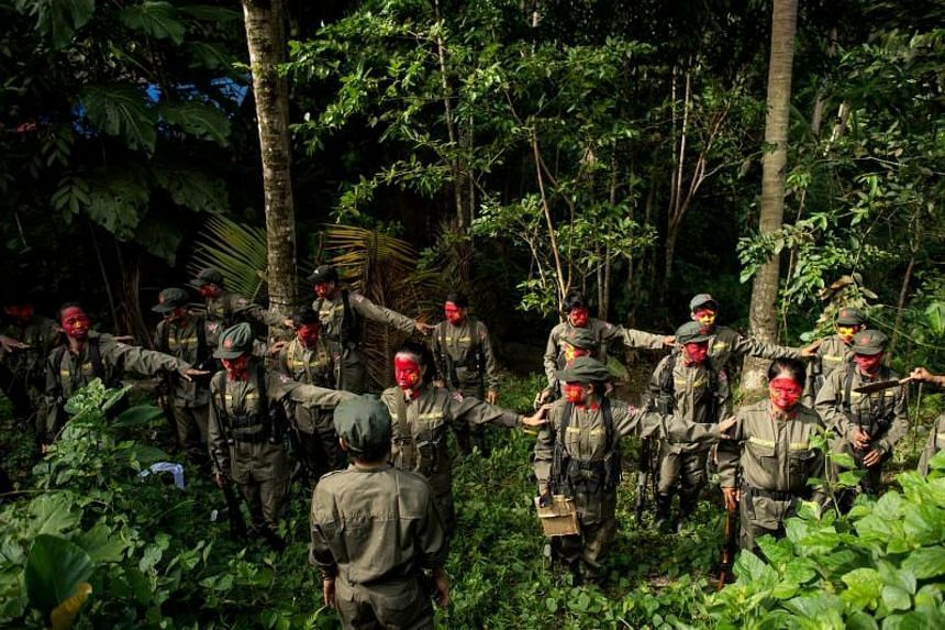 Guerrillas of the New People's Army stand in formation in the Sierra Madre mountain range, located east of Manila, on July 30, 2017.
