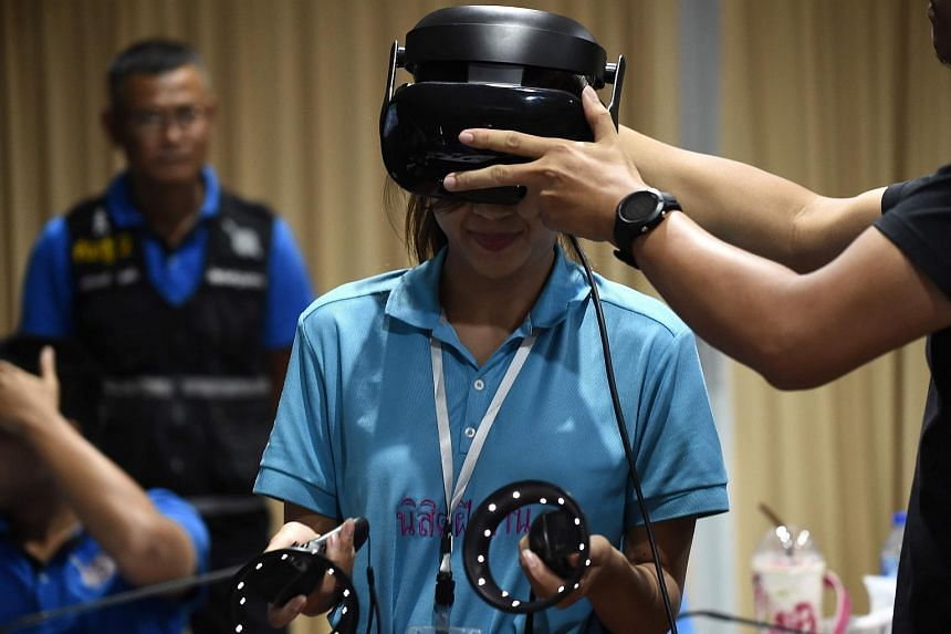 A Thai forensic police officer wearing a virtual reality headset before searching for victims in a simulated city in ruins at the police headquarters in Chonburi province, Thailand.