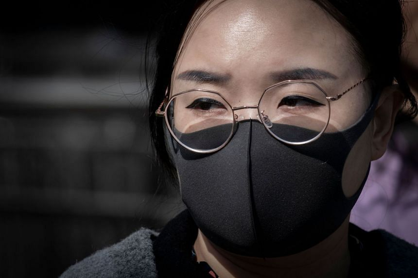 A woman wears a protective mask to reduce the effects of air pollution in Beijing on March 27, 2019.