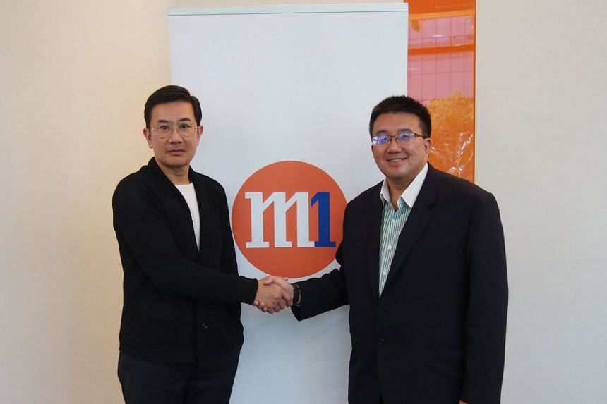 Eddie Chng, DISA group chief executive (left), with Willis Sim, M1 chief corporate sales and solutions officer (right).