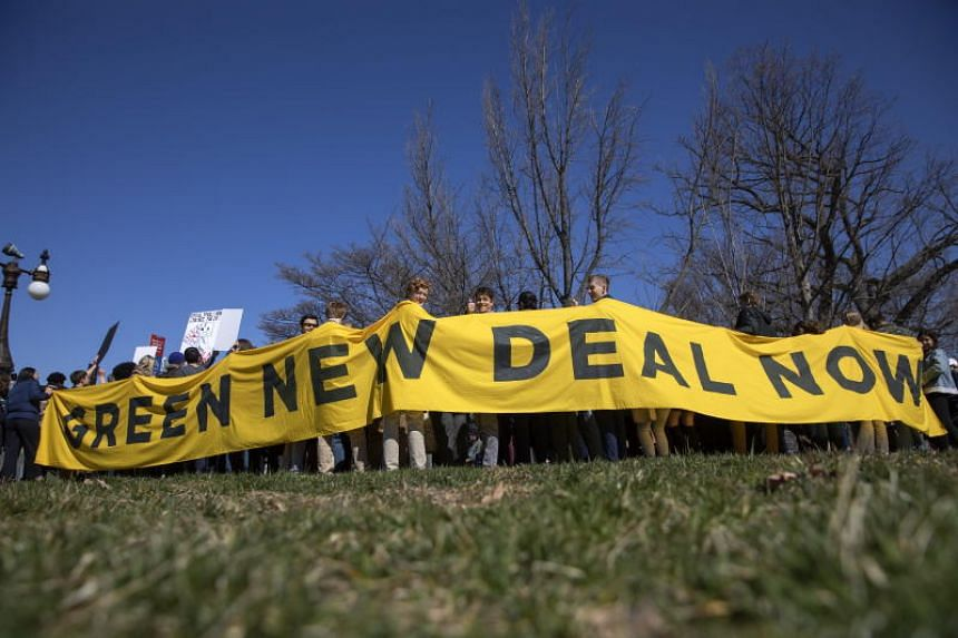 Participants hold a banner while attending a press conference in favour of the Green New Deal at the US Capitol in Washington, DC on March 26, 2019.