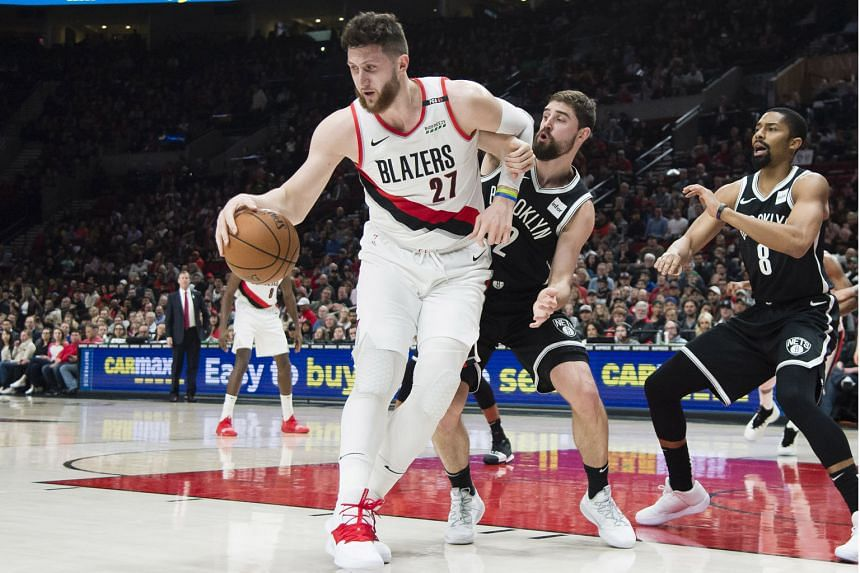 Portland Trail Blazers centre Jusuf Nurkic making a move to the basket against Brooklyn Nets forward Joe Harris and guard Spencer Dinwiddie (No. 8). The Trail Blazers won the game 148-144 in double overtime and clinched a play-off spot for the sixth conse