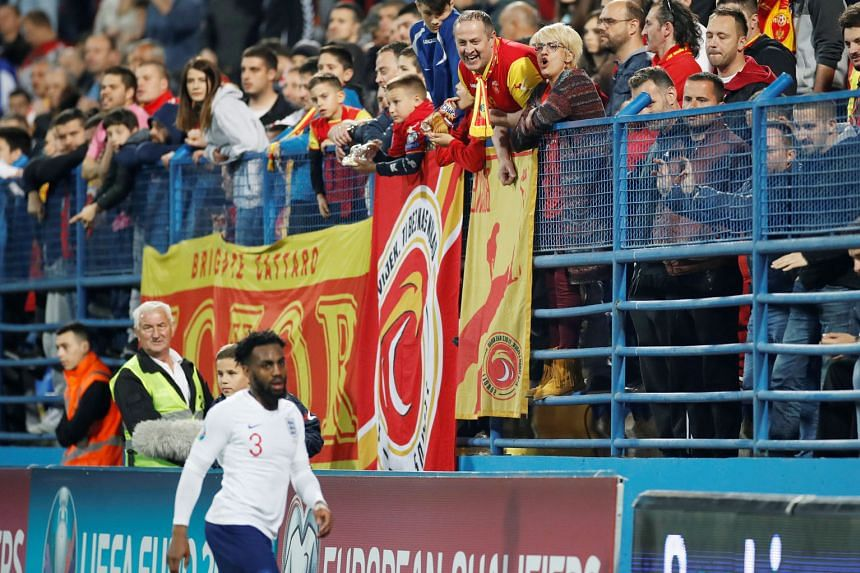 Montenegro fans appearing to goad England left-back Danny Rose during the Three Lions' 5-1 win in Podgorica on Monday. The victory gave Gareth Southgate's men two wins out of two Euro 2020 qualifiers. Below: England forward Raheem Sterling cupping hi