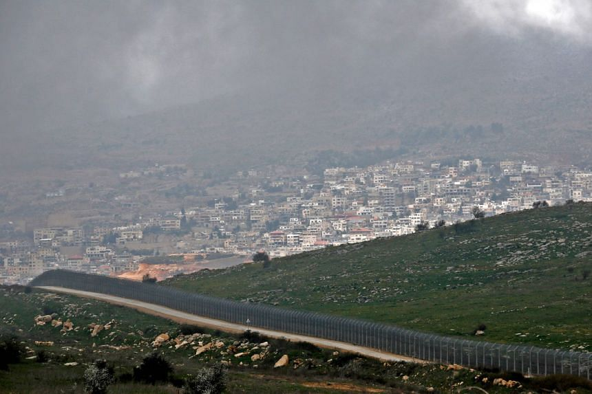 A picture taken on Monday showing the Israeli defensive fence that separates the Israeli-occupied sector of the Golan Heights and the Druze city of Majdal Shams (background) from Syria.