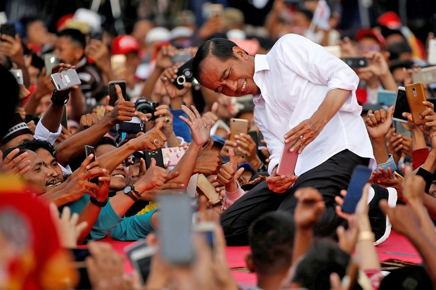 Indonesia's President Joko Widodo taking photos with his supporters during his first campaign rally at a stadium in Banten province on Sunday.