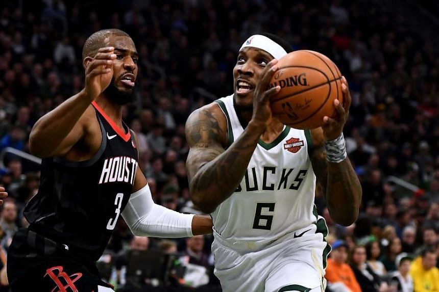Milwaukee Bucks' Eric Bledsoe drives to the basket against Chris Paul of the Houston Rockets during the first half of a game at Fiserv Forum on March 26, 2019.