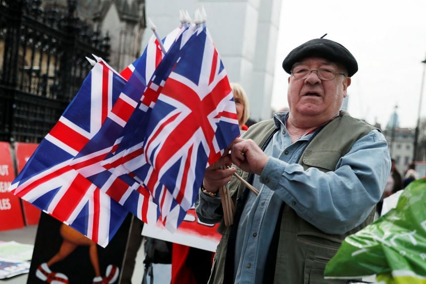 A street vendor selling Union flags passes the Houses of Parliament in London.