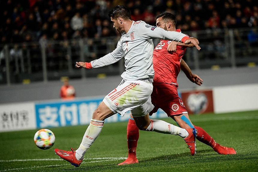 Spain striker Alvaro Morata (in white) playing the ball past Malta defender Zach Muscat to score during the Euro 2020 Group F victory on Tuesday. He also netted the other goal in the 2-0 win to ensure Spain's move to the top of the group.
