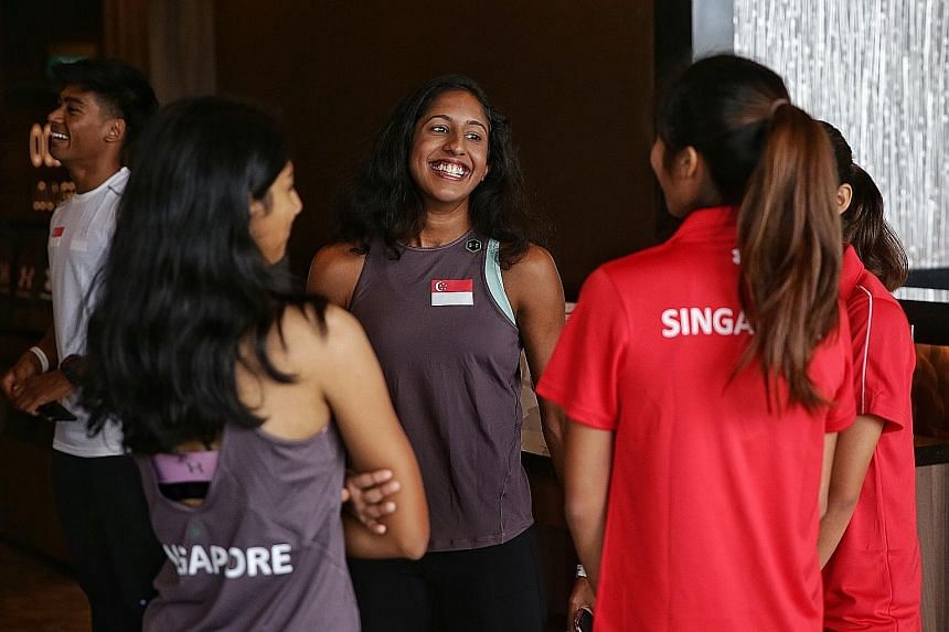 National sprinter Shanti Pereira, 22, chatting with teammates during the launch of the Singapore Open Track and Field Championships at the National Stadium's OCBC Lounge yesterday. She will be competing in the women's 200m and 4x100m mixed relay toda