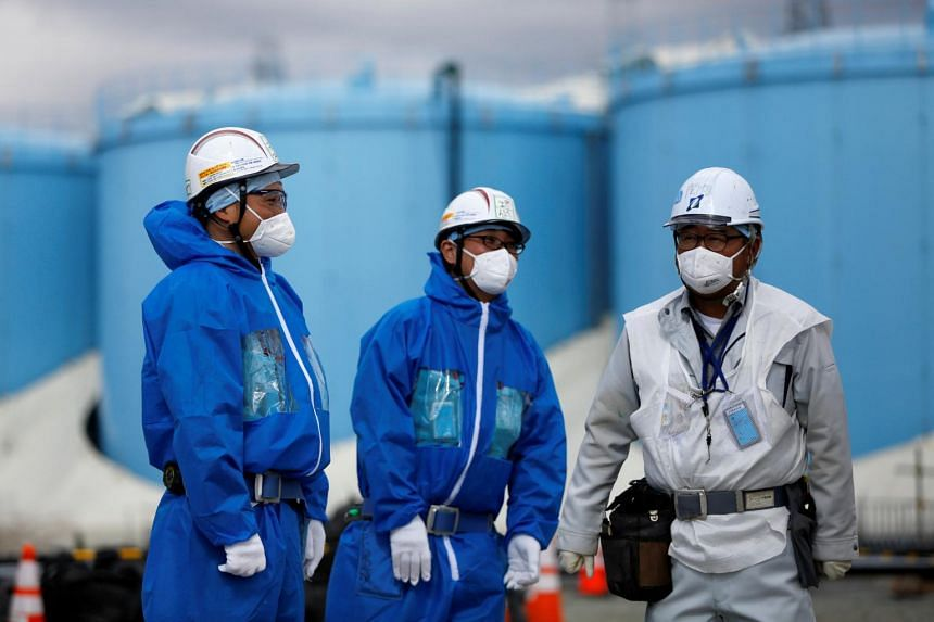 Workers in front of storage tanks for radioactive water at the Fukushima Daiichi nuclear power plant in Okuma town, Fukushima prefecture, on Feb 18, 2019.