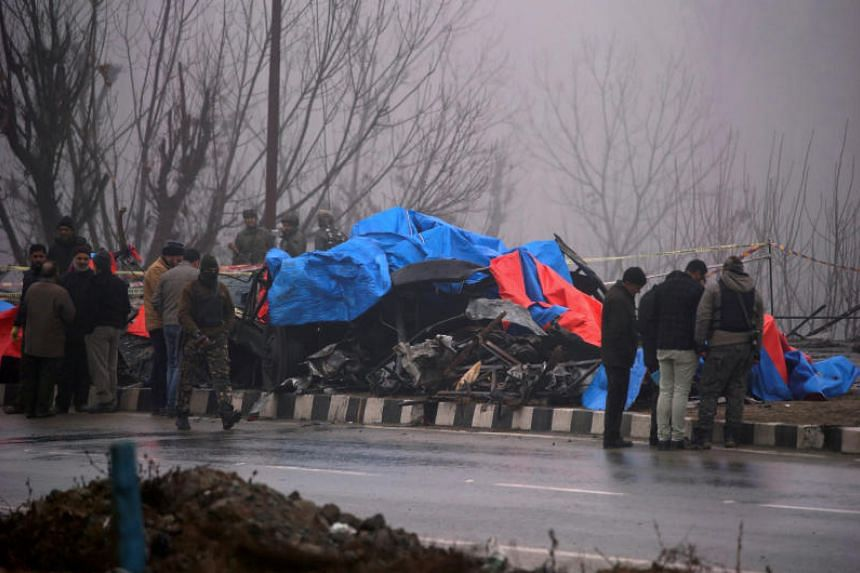 Forensic officials inspect the wreckage of a bus after a suicide bomber rammed a car into the bus carrying Central Reserve Police Force personnel in Lethpora in south Kashmir's Pulwama district, on Feb 15, 2019.