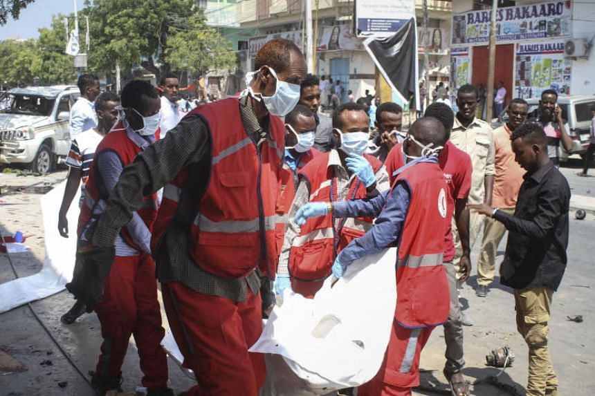 Medics carrying the body of a victim of a car bomb explosion near a hotel in Mogadishu on March 28, 2019.