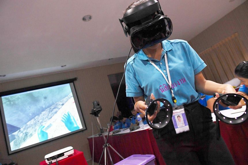 A Thai forensic police officer using a virtual reality headset to search for victims in a simulated city in ruins.