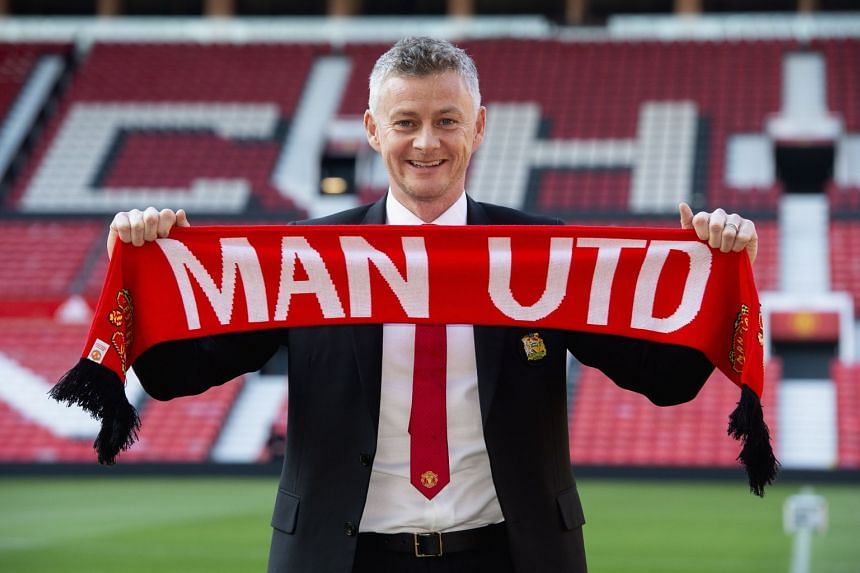 Solskjaer poses for photos at Old Trafford after being announced as the new manager of Manchester United.