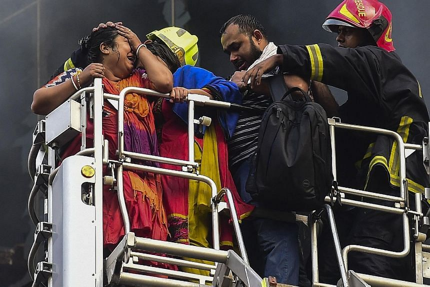 A Bangladeshi survivor reacting after being rescued by firefighters from a burning office building in Dhaka yesterday.