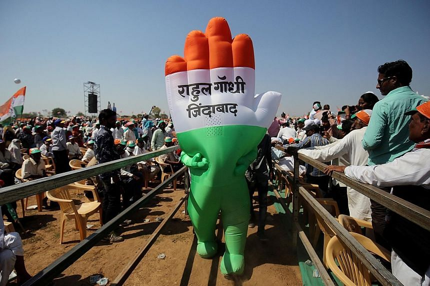 """A supporter wearing an inflatable symbol of India's opposition Congress party at a public meeting in Gandhinagar in Gujarat earlier this month. The words read: """"Long live Rahul Gandhi""""."""