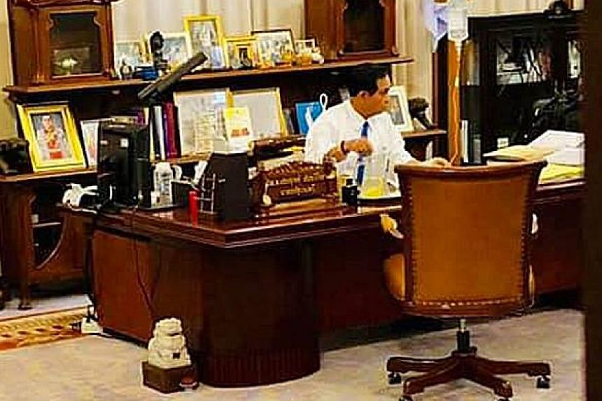 Prime Minister Prayut Chan-o-cha is pictured receiving an intravenous saline infusion while working at Government House yesterday.