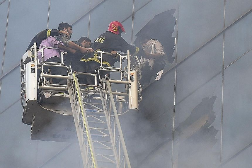 Firefighters rescuing a person from the burning office building in Bangladesh's capital city. A person trying to climb down Dhaka's FR Tower to escape a fire which broke out inside the building yesterday. A large crowd outside the 22-storey office bu