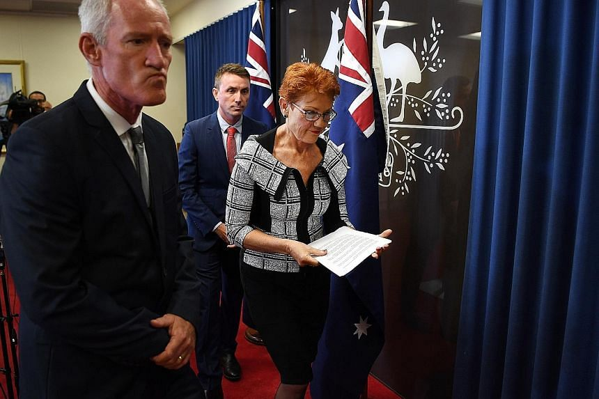 Australia's One Nation leader Pauline Hanson, flanked by party officials Steve Dickson (left) and James Ashby, after a press conference yesterday over the two men's involvement in a scandal over soliciting funds from a US lobby in return for weakenin