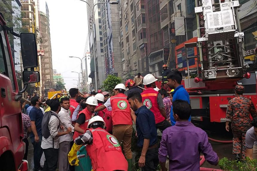 Bangladeshi Red Crescent volunteers preparing to provide first aid after a blaze broke out in an office building in Dhaka on March 28, 2019.