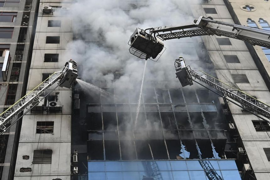 Bangladeshi firefighters on ladders work to extinguish a blaze in an office building in Dhaka on March 28, 2019.