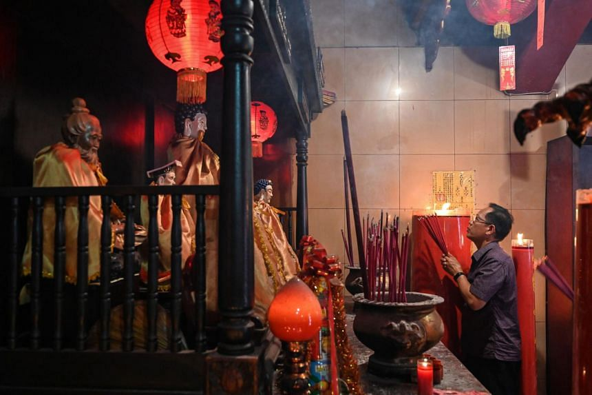 An Indonesian man holding burning incense at a temple in Jakarta, on Feb 19, 2019.