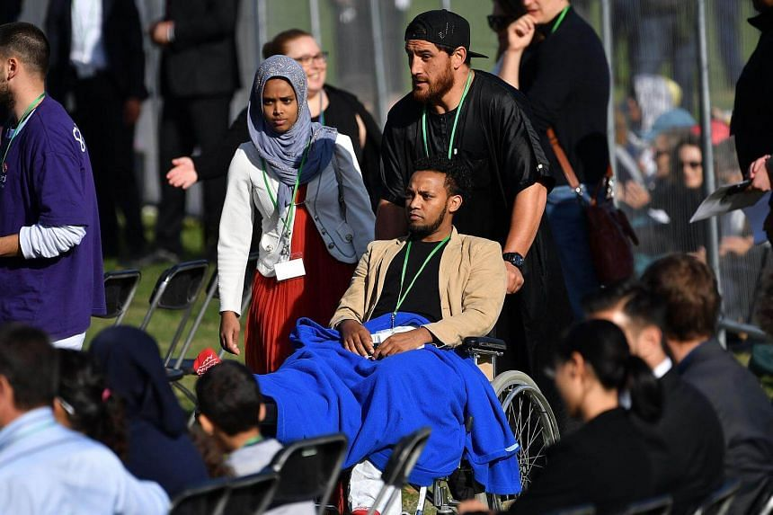 A man is wheeled into the family area in front of the stage during the ceremony.