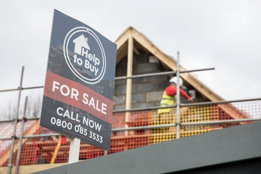A sign advertising a property for sale under the government's Help To Buy scheme stands next to a building site in London, UK, on March 26, 2019.