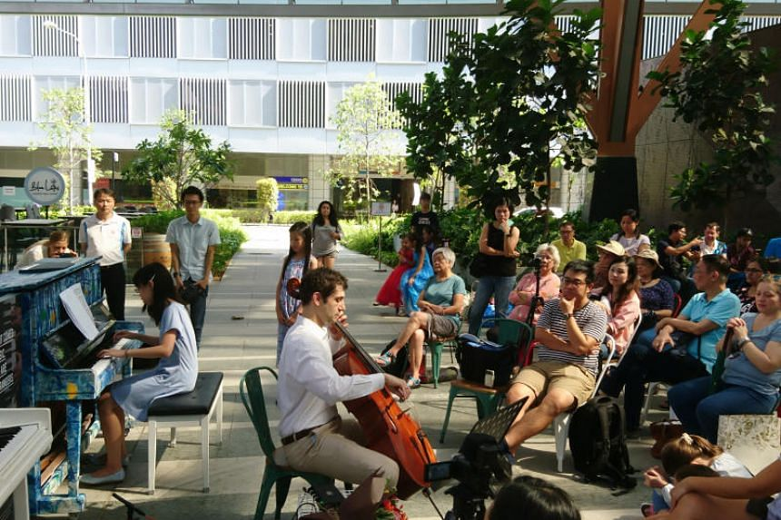 A group of music lovers putting on a free mini concert for the public using a public piano from Play It Forward Singapore's initiative.