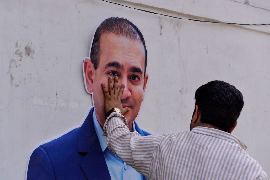 A Congress Party supporter puts his hand on an image of Nirav Modi during a protest in New Delhi.