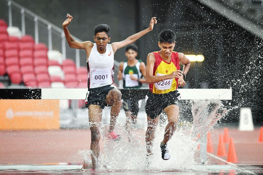 Ruben Loganathan (white top) and Joshua Rajendran locked in battle before the ASRJC runner surged ahead to win the A Div boys' 3,000m steeplechase in 10:24.85 at the National Stadium yesterday.
