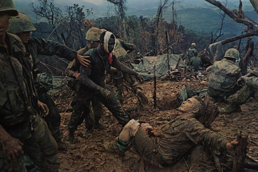 An injured US Marine is drawn to his comrade in British photographer Larry Burrows' famous photo Reaching Out (1966).