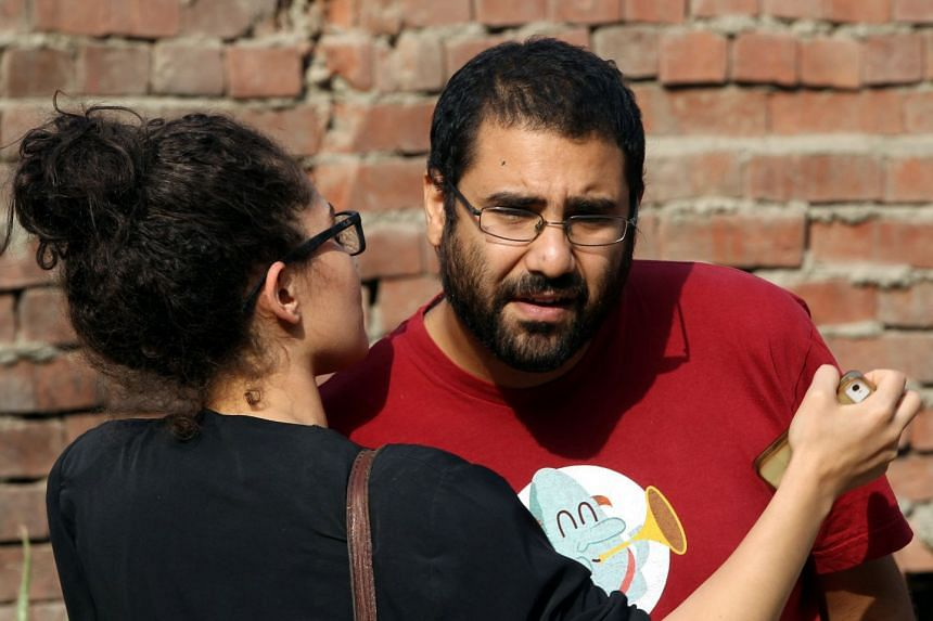 Alaa Abdel-Fattah (right) and an unidentified person react after hearing a court sentence against his sister, Sanaa Saif al-Islam, in 2014